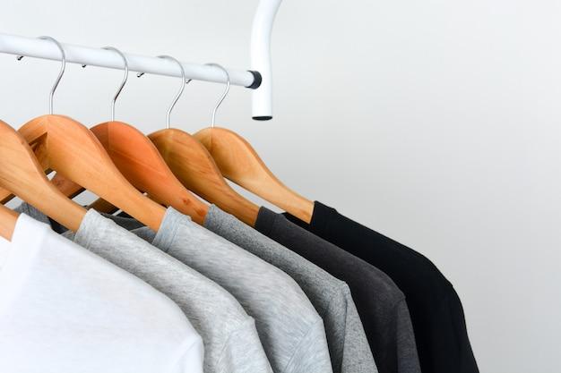 木製ハンガーに掛かっている黒、グレーと白の色のtシャツ Premium写真