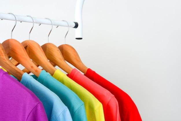 白い背景の上に木製の洋服ハンガーに掛かっているカラフルなレインボーtシャツ Premium写真