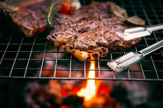 Гриль t костяной стейк на пылающий гриль Premium Фотографии