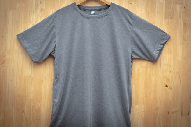 グレーの半袖tシャツプレーンラウンドネックの概念のアイデア木製バックグラウンドフロントビュー Premium写真