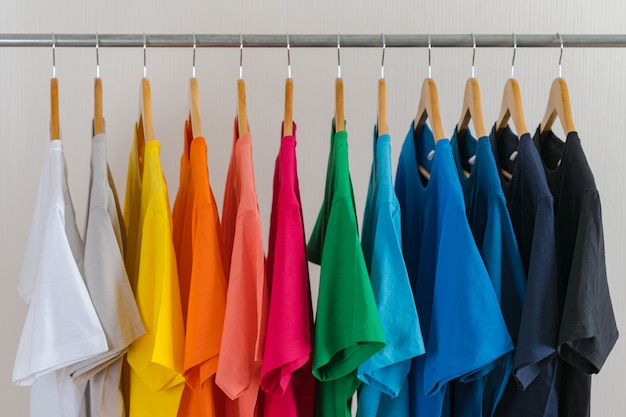 ハンガー、アパレルの背景にカラフルなtシャツのクローズアップ Premium写真