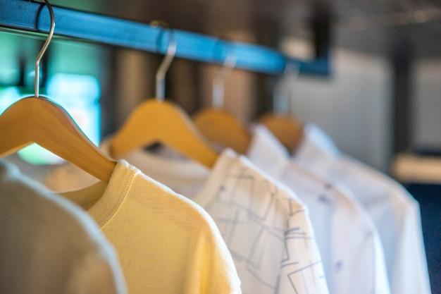ワードローブのレールに掛けられた白いtシャツ、インテリアデザイン。インテリア。 Premium写真