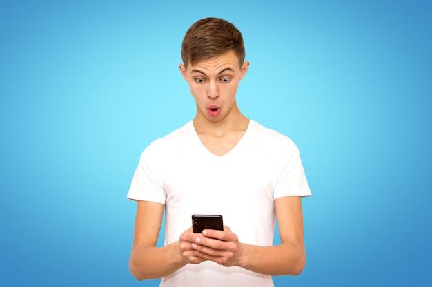 電話、分離、電話とスタジオで青い背景上の男の白いtシャツで驚いた男 Premium写真