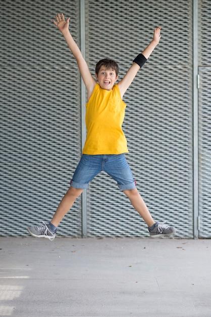 黄色のtシャツを着ているとジャンプの若いティーン Premium写真