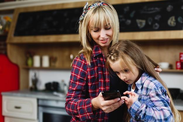 同じtシャツの魅力的なお母さんと娘は、スマートフォンで何かを見ます 無料写真