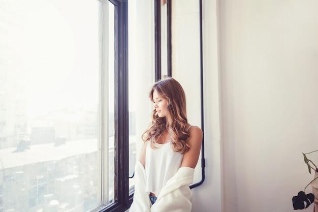 窓の近くのtシャツの女 Premium写真