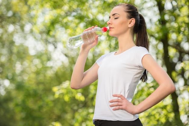 白いtシャツ飲料水で美しいスポーティな女の子。 Premium写真
