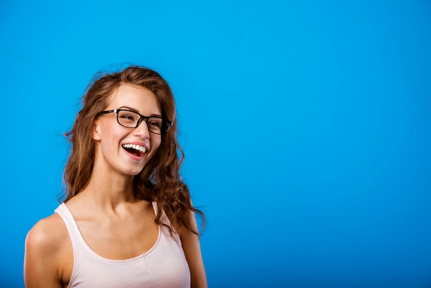 Tシャツとメガネの女の子は笑って笑っています。 Premium写真