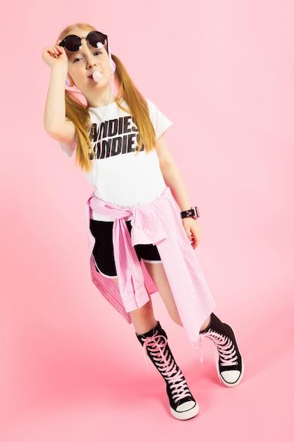 ショートパンツ、tシャツ、ハイスニーカーの美しい少女の肖像画。 Premium写真