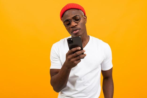 白いtシャツを着たハンサムなアフリカ人が黄色の背景にソーシャルネットワークで通信します。 Premium写真