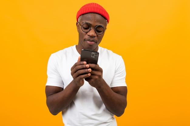 白いtシャツを着たハンサムなアフリカ人が黄色の電話でソーシャルネットワークで通信します。 Premium写真