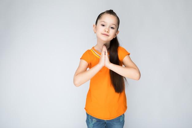 オレンジ色のtシャツとブルージーンズの女の子 Premium写真
