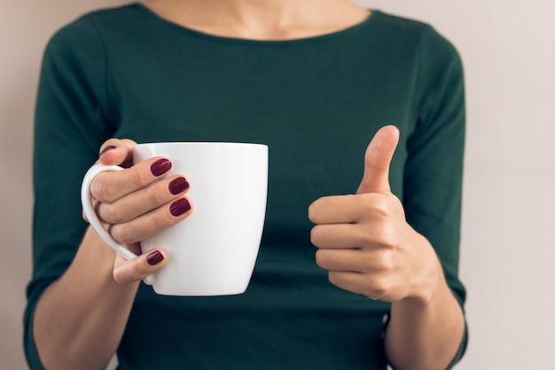 緑のtシャツと白いカップを押しながら親指を現してあずき色のマニキュアの女 Premium写真