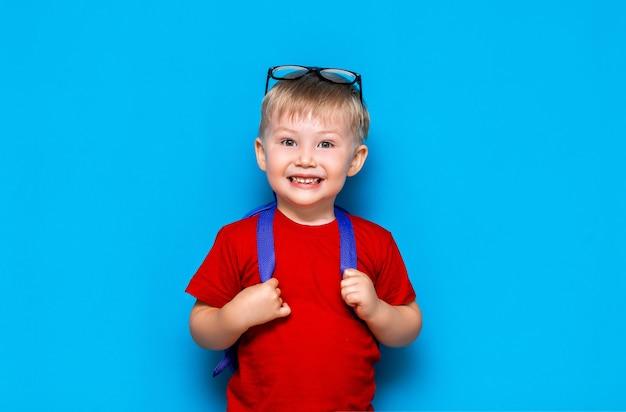 彼の頭の上に眼鏡をかけて赤いtシャツで幸せな微笑む少年は初めて学校に行きます。ランドセルを持つ子供。キッド Premium写真