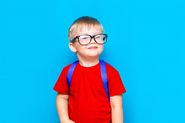 メガネの赤いtシャツで幸せな微笑む少年は初めて学校に行く予定です。ランドセルを持つ子供。学校に戻る Premium写真