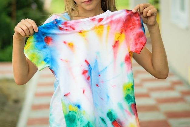 少女はネクタイ染料のスタイルで描かれたtシャツを試着します。 Premium写真