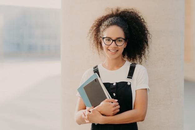 愛らしい巻き毛の女子学生は白いカジュアルなtシャツとオーバーオールを着て、メモ帳や教科書を保持 Premium写真