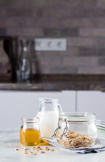 朝食用食品のコンセプト。自家製グラノーラ、ミルク、または台所のテーブルtabckground Premium写真