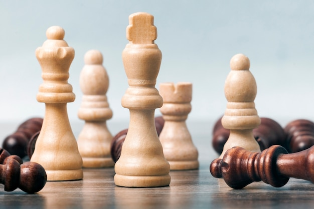 On the table are white chess pieces. the king's figure is in focus in the center; the remaining figures are out of focus. around them are black pieces. the concept of business, Premium Photo
