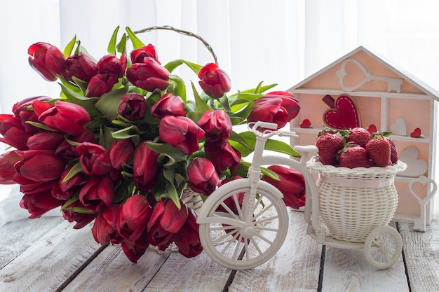 On the table in a basket there are a lot of red tulips and a basket with strawberries Premium Photo