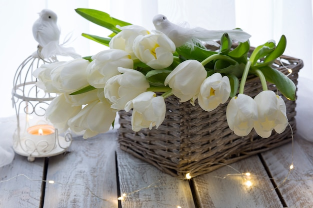 On the table a basket with white tulips, white birds and a candlestick , lights Premium Photo