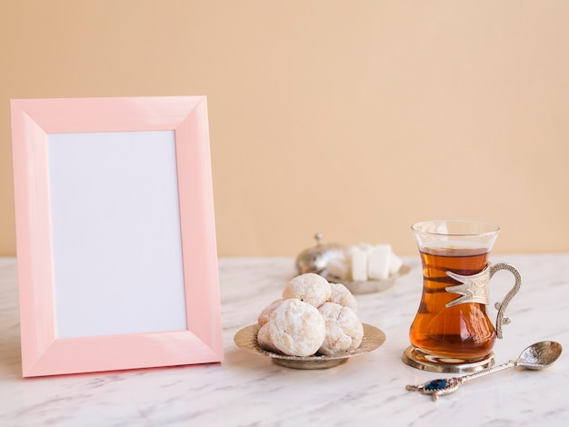 Table composition with tea, pastries and frame Free Photo