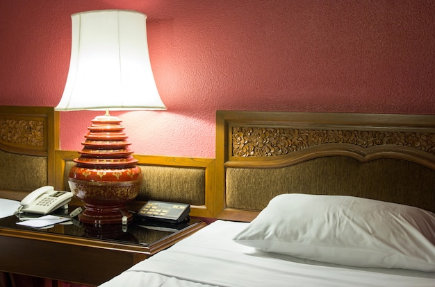 Table lamp in the bedroom at night time Premium Photo