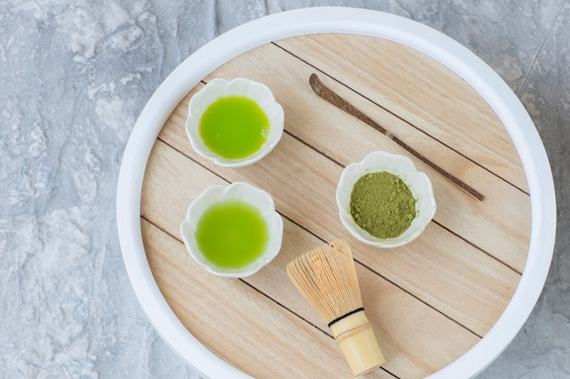On the table matcha tea in drinking bowls, a tea whisk and a spoon Premium Photo