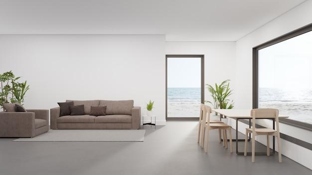 현대 비치 하우스 또는 고급 호텔에서 거실과 소파 근처의 넓은 식당의 콘크리트 바닥에 테이블. 프리미엄 사진