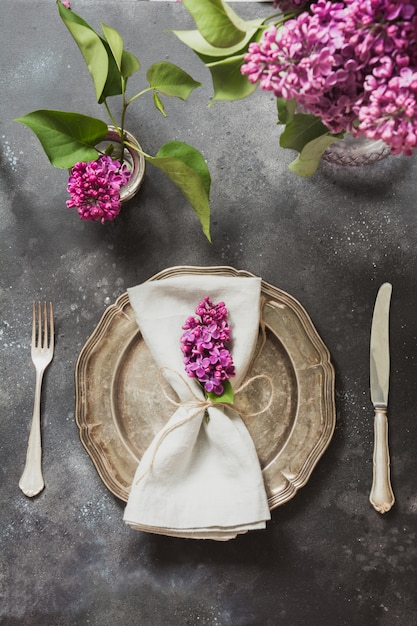 Table place setting with pink lilac flowers, silverware on vintage background. Premium Photo