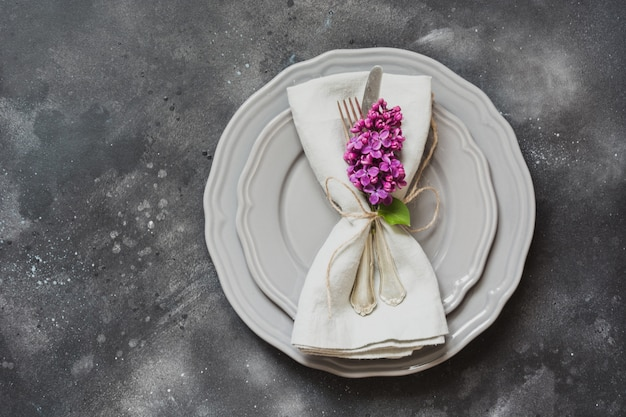 Table place setting with purple lilac flowers, silverware on vintage background. Premium Photo