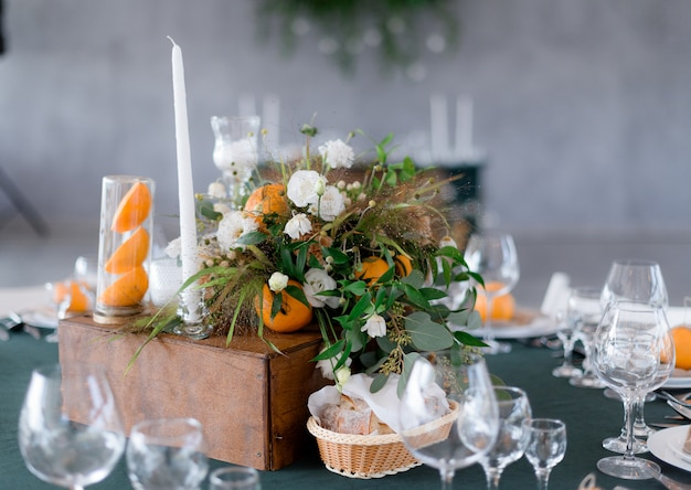 Table serving with floral composition with oranges on the green table in the restaurant Free Photo