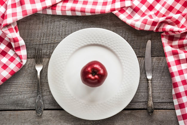Table set with red apple on white plate with knife and fork with red checkered napkin. Premium Photo