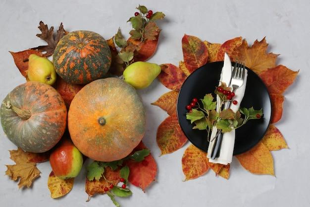 추수 감사절에 테이블 설정은 호박, 가막살 나무속, 배 및 회색 표면에 화려한 잎 장식. 평면도 프리미엄 사진