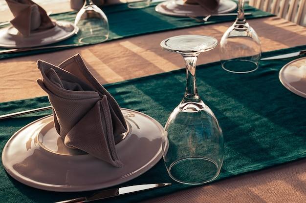 Сервировка стола в ресторане на открытом воздухе, вечерние лучи солнца Premium Фотографии