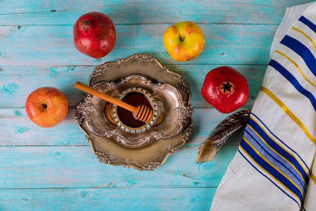 On the table in the synagogue are the symbols of yom kippur apple and pomegranate, shofar talith Premium Photo