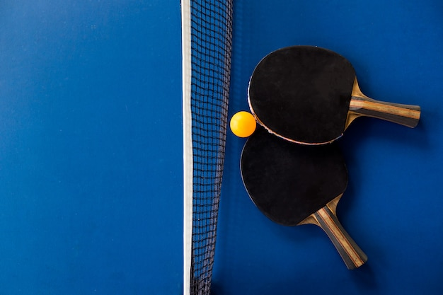 Table tennis racket and ball on blue background. Premium Photo