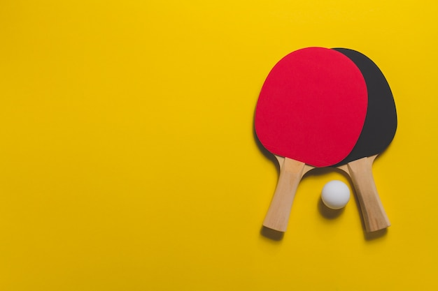 Table Tennis Rackets On Yellow Surface Photo Free Download