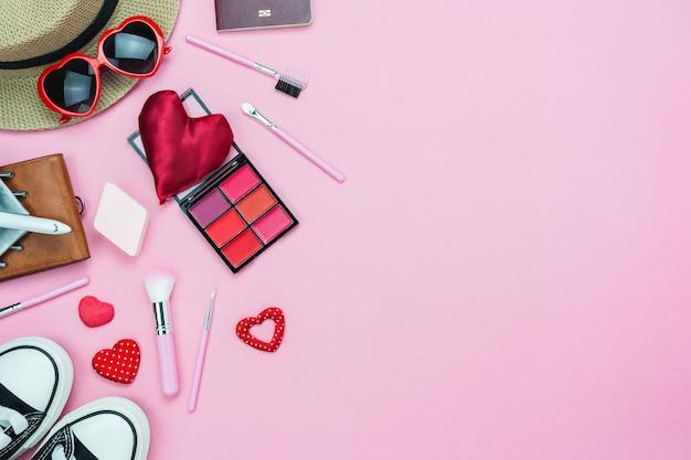 バレンタインの日の装飾と女性の化粧品のテーブルトップビュー。 Premium写真