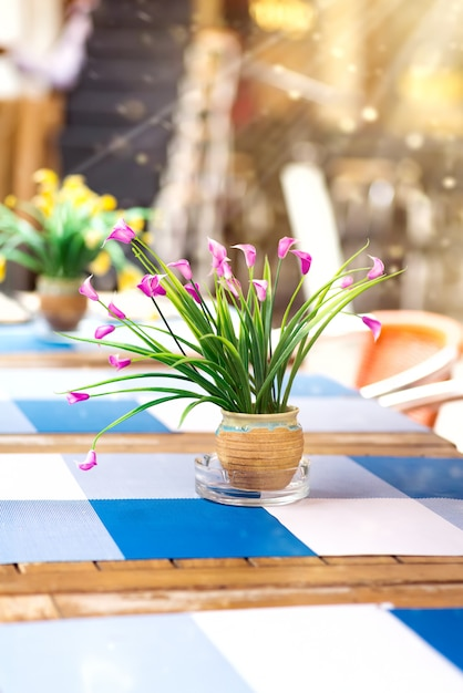 Table with flowers and chairs in street cafe. Premium Photo
