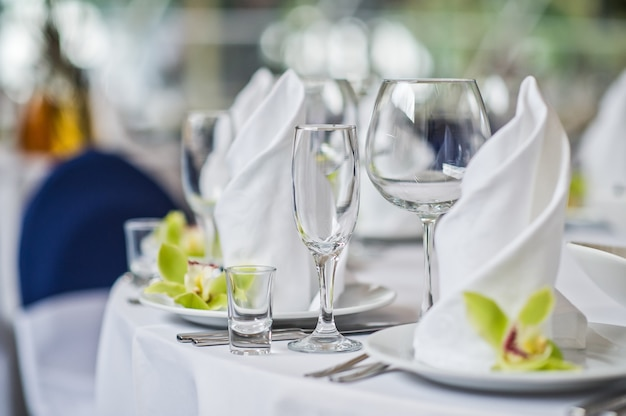 Table with glasses, plates and white napkins, green flower, dinner in the restaurant Premium Photo