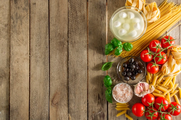 Table with ingredients to prepare italian pasta Free Photo