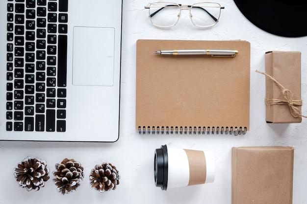 Tavolo con cose sullo stile di vita. computer portatile, blocco note con una penna, una tazza di caffè, occhiali e decorazioni. vista dall'alto Foto Gratuite