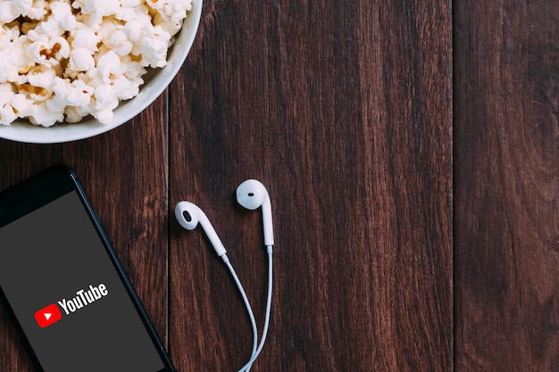 Table with popcorn bottle and youtube logo on apple iphone and earphone. Premium Photo