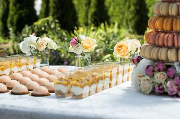 花とマカロンケーキとカップで軽いデザートで飾られたお菓子のテーブル Premium写真