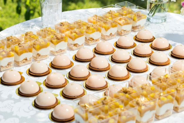 Стол со сладостями, украшенный цветами и макарунами, и легкие десерты в чашках Premium Фотографии