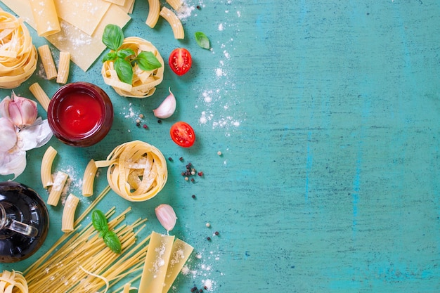 Table with variety of pasta and tomato sauce Free Photo