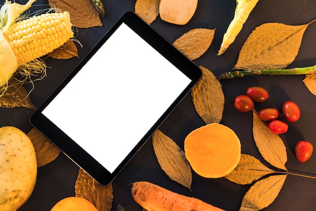 Table with vegetables and tablet Free Photo
