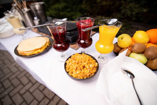 A table with a white tablecloth, pancakes and three glasses with a filling. camping Premium Photo
