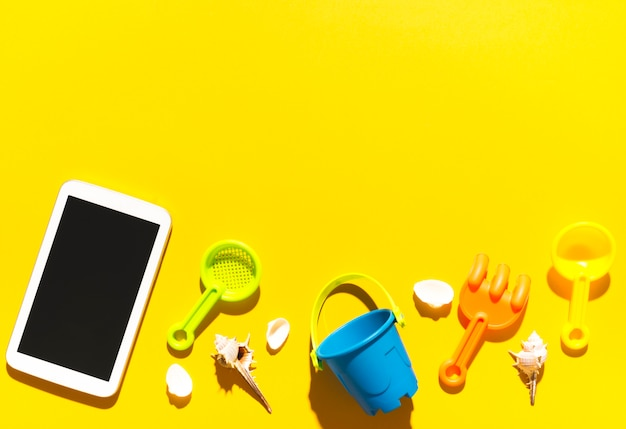 Tablet and beach toys on colorful surface Free Photo